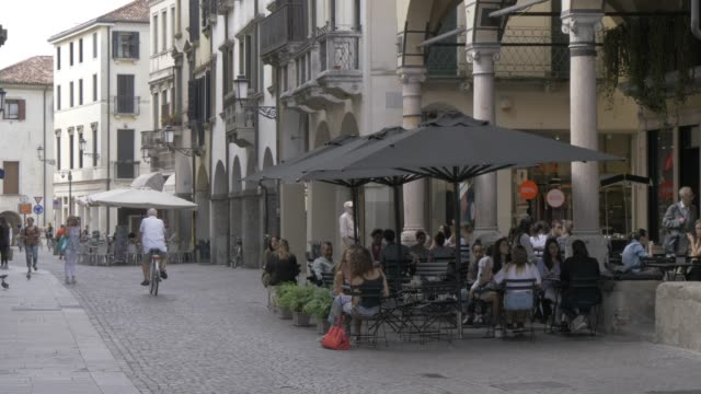 view of cafe restaurant, cyclists and people on via umberto l, padua, veneto, italy, europe - ワイドショット点の映像素材/bロール
