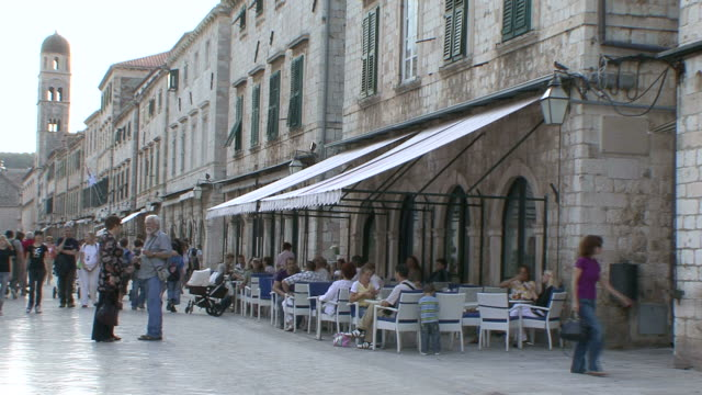 ws view of cafe with strollers going at stradun in dubrovnik,  unesco world heritage site / dubrovni, croatia  - pavement cafe stock videos & royalty-free footage