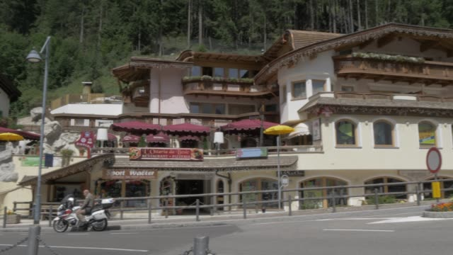 view of cafes and bars along main road in canazei, fassa valley, province of trento, south tyrol, italian dolomites, italy, europe - canazei video stock e b–roll
