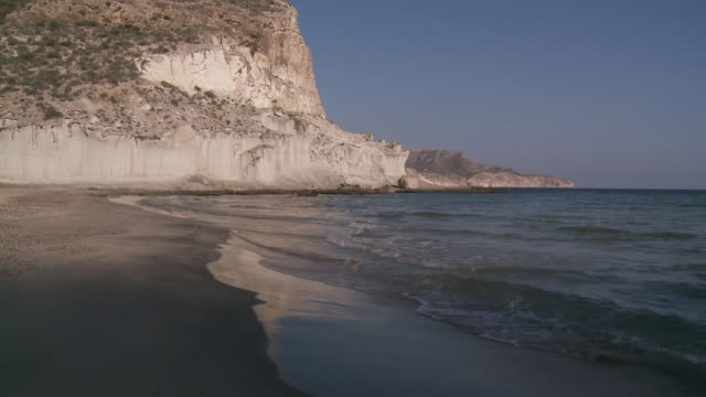 ws view of cala de enmedio beach and volcanic cliffs / agua amarga, andalusia - agua点の映像素材/bロール