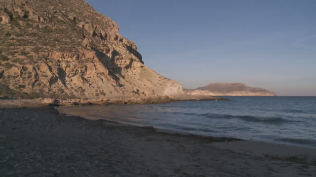 ws view of cala del plomo coastline at sunset near cabo de gata natural park / agua amarga, andalusia, spain - agua点の映像素材/bロール