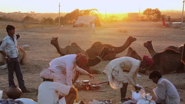 MS View of Camel herdsman at sunset gathering in groups Camel Fair / Pushkar, Rajasthan, India