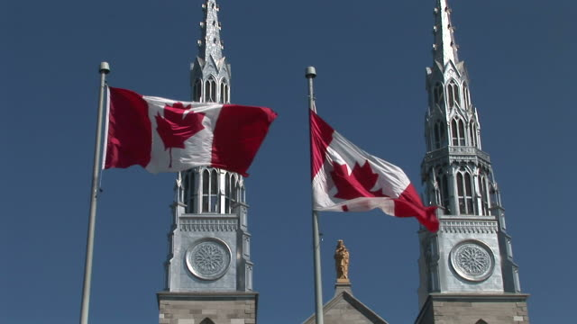 stockvideo's en b-roll-footage met view of canadian flag flapping in front of parliament of ottawa canada - parliament building