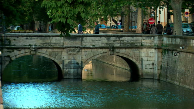 ws zo view of canal and arch bridge with traffic / nimes, languedoc, france - arch bridge stock videos & royalty-free footage