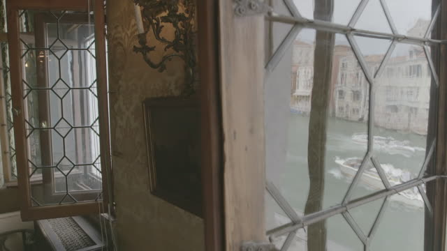 ms view of canal and city through window glass of palazzo contarini / venice, italy - palace stock videos & royalty-free footage