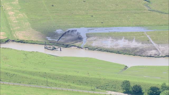 aerial ws view of canal clean machine  / eiderstedt, schleswig-holstein, germany - wasserverschmutzung stock-videos und b-roll-filmmaterial