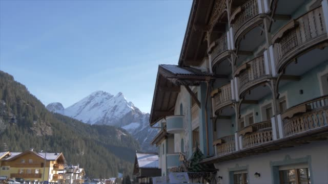 view of canazei chalets and mountains on sunny day in winter, province of trento, italian dolomites, italy, europe - canazei video stock e b–roll