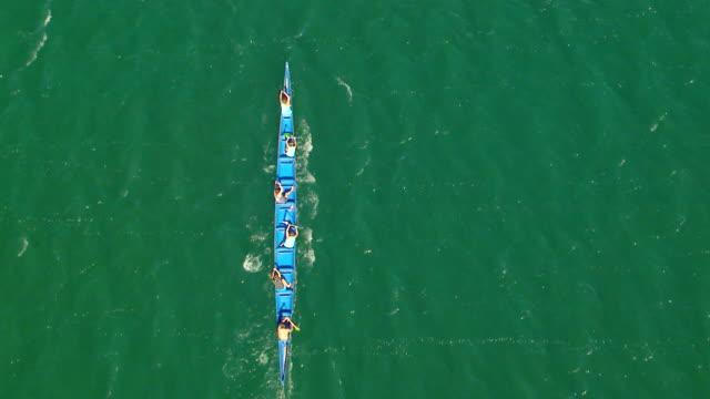 vídeos de stock e filmes b-roll de ws aerial zo view of canoe racing with six men paddling / neah bay, washington, united states - remo com par de remos