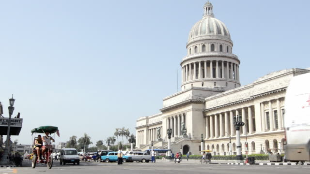 ws view of capitol building and passing vehicle in road with people / havana, cuba - la havana video stock e b–roll