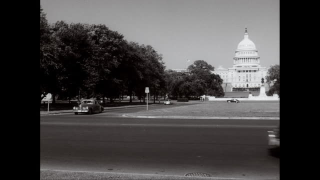 ws view of capitol building, cars moving in foreground / washington dc, united states - governo video stock e b–roll