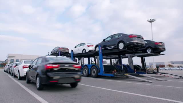 stockvideo's en b-roll-footage met view of car carrier trailer unloading cars in parking lot at pyeongtaek port - scheepvaart