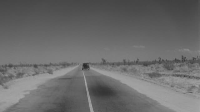 ws pov view of car driving down paved road, looking straight forward through desert - joshua tree stock videos and b-roll footage