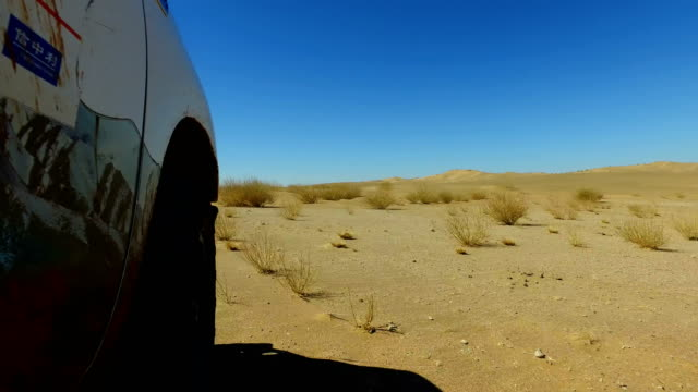 view of car driving on gobi desert/inner mongolia, china. - 4x4 stock videos & royalty-free footage