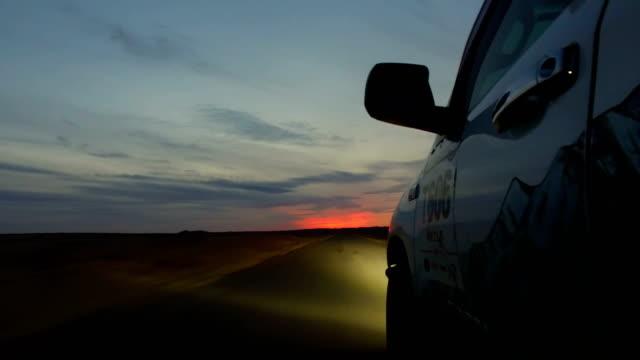 View of car driving on road through gobi desert at sunset/Inner Mongolia, China.