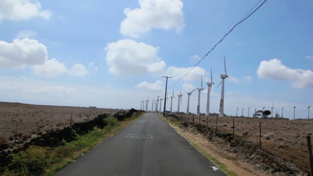 vidéos et rushes de ws pov t/l view of car driving through south point road with row of windmills on roadside / south point, hawaii, usa - big island îles hawaï