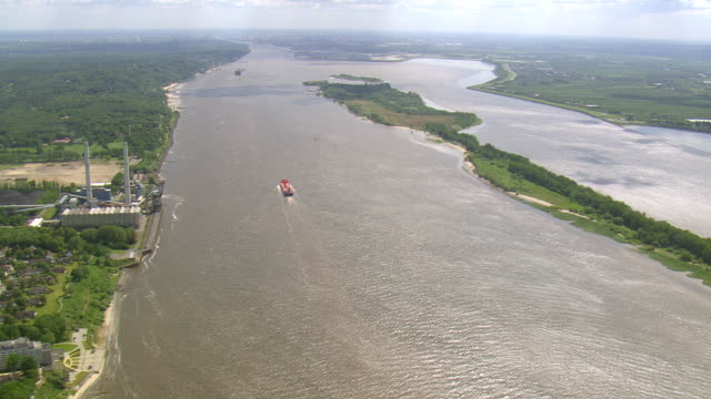 ws aerial view of cargo ship moving in river with forest and town along coast / germany - küste stock-videos und b-roll-filmmaterial