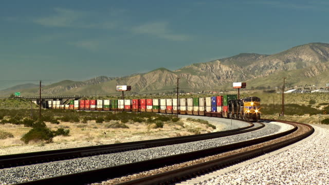 ws view of cargo train passing with mountain in background / palm springs, california, usa - cargo train stock videos & royalty-free footage