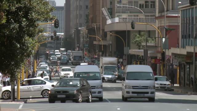 stockvideo's en b-roll-footage met ws t/l view of cars driving along busy street in cbd / johannesburg, gauteng, south africa - johannesburg