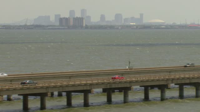 WS AERIAL TS View of cars driving on lake ponchartrain causeway with downtown / New Orleans, Louisiana, United States