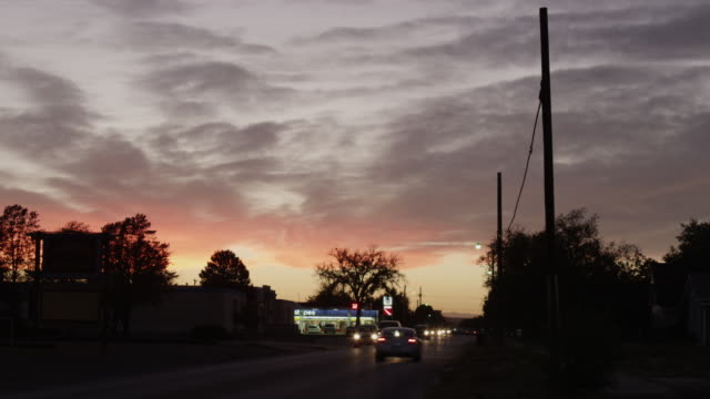 ws view of cars driving on road with orange clouds at sunset / roswell, new mexico, united states - roswell stock videos & royalty-free footage