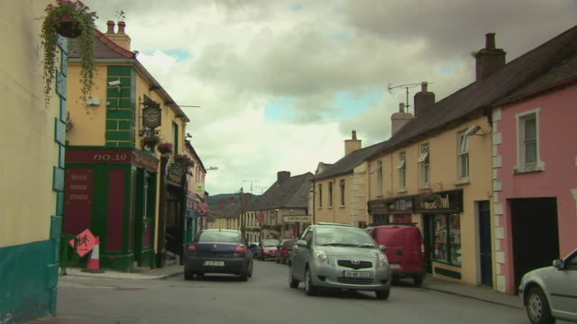 WS View of cars going by row of shops / Rathdum, Ireland