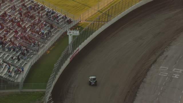 ms aerial zi view of cars moving around race track with man waving flag at dodge city raceway park / kansas, united states - 2012 stock videos & royalty-free footage