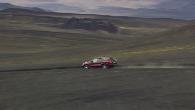 ws aerial view of cars moving on dusty lava field / iceland - 20 seconds or greater stock videos & royalty-free footage