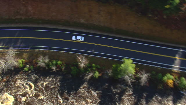MS AERIAL TS PAN View of cars moving on Kancamagus Scenic Highway near river / New Hampshire, United States