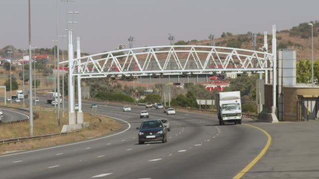 ws r/f view of cars on highway passing through toll gantry / johannesburg, gauteng, south africa - dissolvenza in chiusura video stock e b–roll