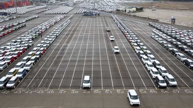 view of cars parking in a row and some cars running at export pier of sinhangman - repetition stock videos & royalty-free footage