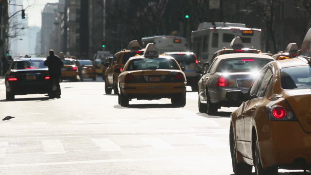 WS View of cars running at Fifth avenue with pedestrians and Cars crossing Avenue / New York, United States
