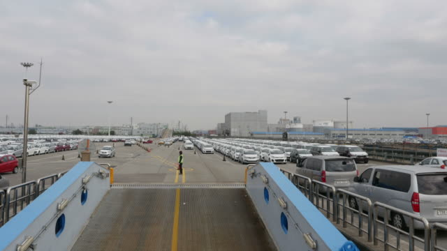 view of cars running into cargo ship and large group of cars parking in a row at pyeongtaek port - 自動車産業点の映像素材/bロール