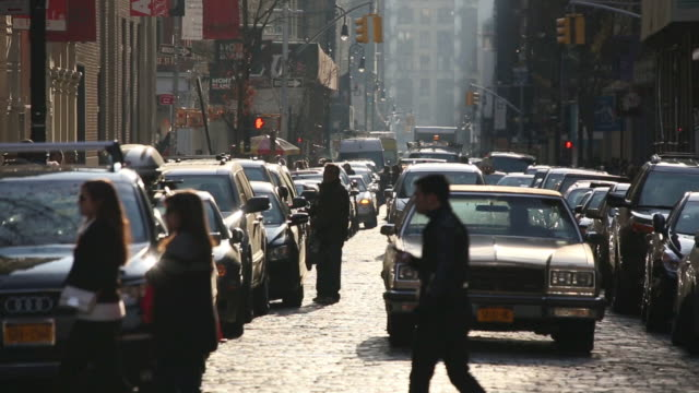 WS TU View of cars running on shining stone pavement street / New York, United States