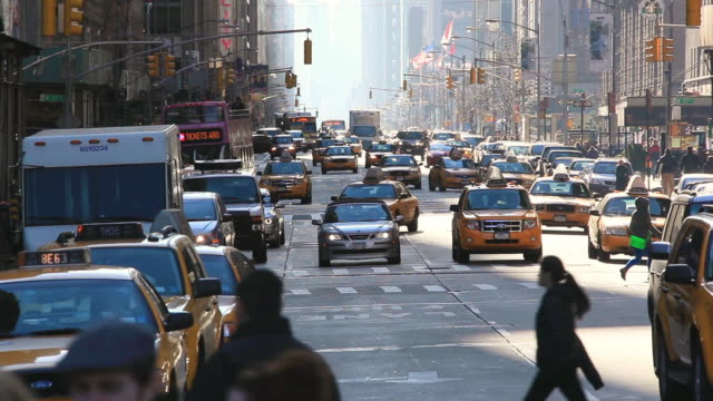WS TU View of cars running on sixth avenue and pedestrians crossing the crosswalk with traffic and skyscraper / New York, United States