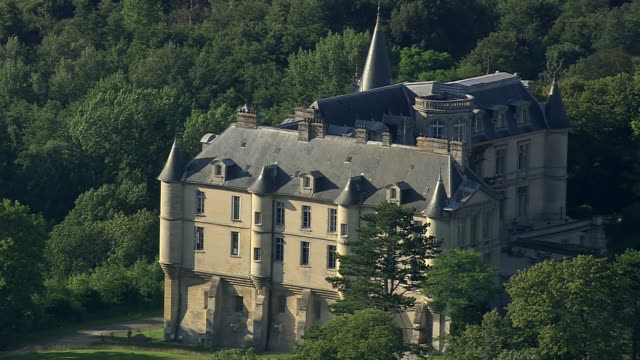 MS AERIAL View of castle of Mello surrounded by trees with village / Picardy, France
