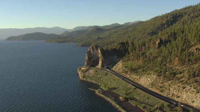 ws aerial view of cave rock tunnel entrance with cars driving in and golden sunlight / lake tahoe, nevada, united states - seeufer stock-videos und b-roll-filmmaterial