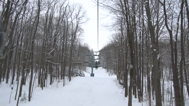 ms pov view of chairlift on ski hill with man skiing underneath chair / ellicottville, new york, united states  - inquadratura dalla sciovia video stock e b–roll