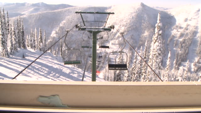 tu view of chairlift through lift shack window / nelson, british columbia, canada - seggiovia video stock e b–roll