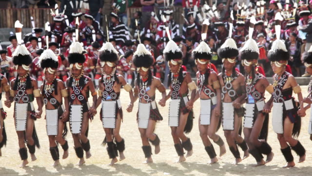 vídeos de stock e filmes b-roll de ws view of chang tribesmen wearing traditional dress hornbill dancing festival audio / nagaland, india - dança tradicional