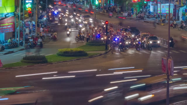 MS T/L View of chaotic traffic moving at busy roundabout (circle of death) at night / Ho Chi Minh City - Saigon, Vietnam