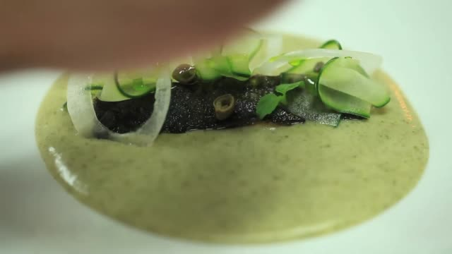 view of chef pouring a sauce on a broiled fish and the garnish in a plate - garnish stock videos & royalty-free footage