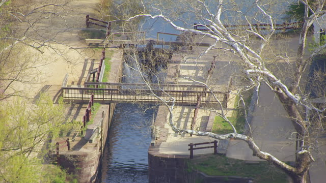 ms aerial pov view of chesapeake and ohio canal national park and great falls tavern visitor center and towpath / great falls, virginia, united states - chiusa di fiume video stock e b–roll