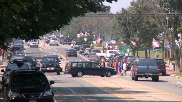 ws view of children crossing main street, lots of american flags roadside / montauk, new york state, united states - long island video stock e b–roll