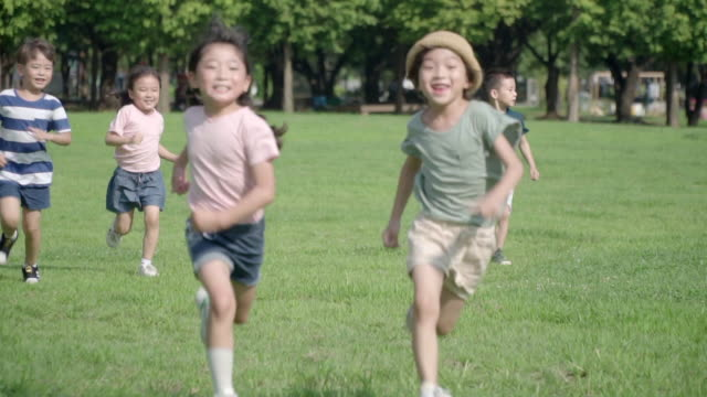 view of children doing track and field in summer at seoulforest (the third largest park in seoul city) - five people stock-videos und b-roll-filmmaterial
