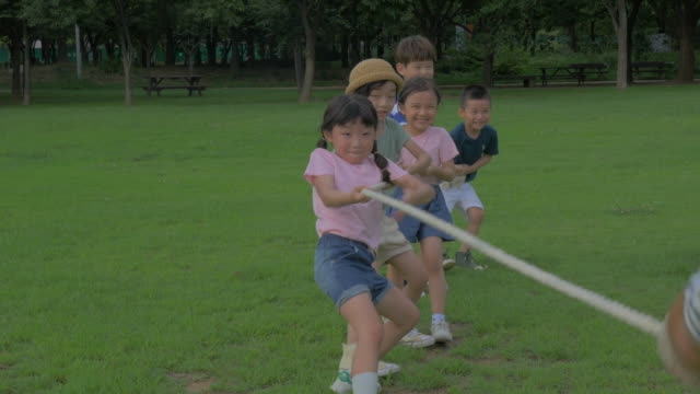 vídeos de stock e filmes b-roll de view of children doing tug-of-war (game: pulling rope) in summer at seoulforest (the third largest park in seoul city) - corda