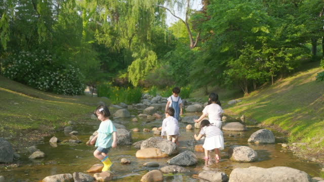 view of children enjoying their time in the stream - 水遊び点の映像素材/bロール