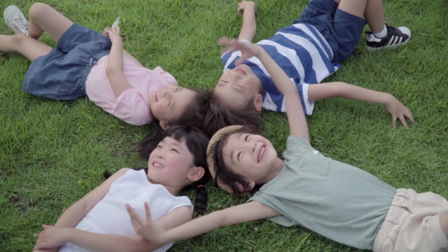 view of children lying on the lawn with smile in summer at seoulforest (the third largest park in seoul city) - 芝生点の映像素材/bロール
