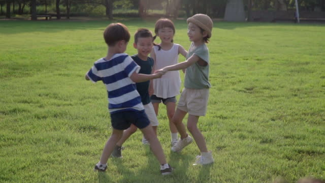 view of children making a cirle by holding hands in summer at seoulforest (the third largest park in seoul city) - 50 seconds or greater stock videos & royalty-free footage
