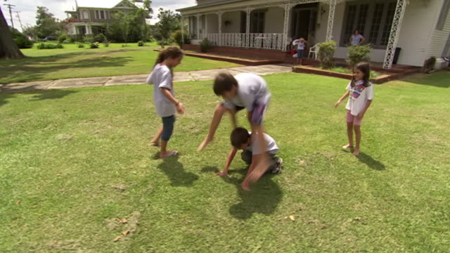 ws ts view of children playing leapfrog in their front yard / rayne, louisiana, united states - leapfrog stock videos & royalty-free footage