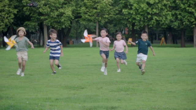 view of children running with pinwheels in summer at seoulforest (the third largest park in seoul city) - windrad stock-videos und b-roll-filmmaterial